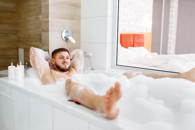 Man liggend in bad met schuim in de ochtend.