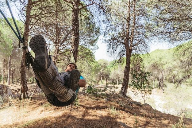 Man liggend in hangmat in bos