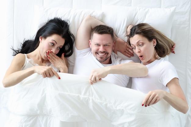 Man liggend met twee geliefden in bed. vrouwen keken onder dekking en vroegen zich af. promiscue seks concept