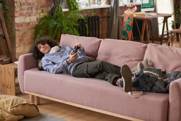 Man liggend op de bank met joystick en videogame spelen tijdens zijn vrije tijd in de kamer