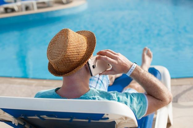 Man liggend op een ligstoel en praten over een telefoon in de buurt van het zwembad
