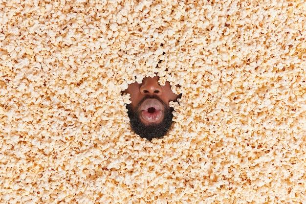 Man ligt in popcorn houdt mond open voelt zich geschokt of verrast eet heerlijk dessert met eetlust kijkt voetbalwedstrijd consumeert smakelijke snack