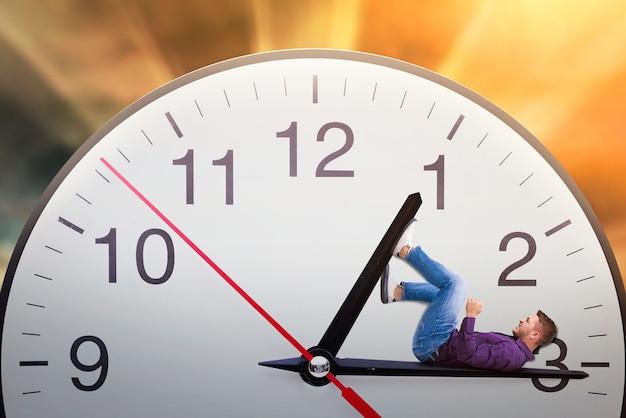Man ligt op de pijl van een enorme klok en probeert de tijd te stoppen. termijnconcept