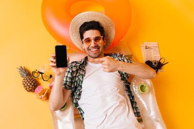 Man ligt op opblaasbare matras op ruimte van ananas, krant en retro camera. man in hoed en bril wijst naar smartphone.
