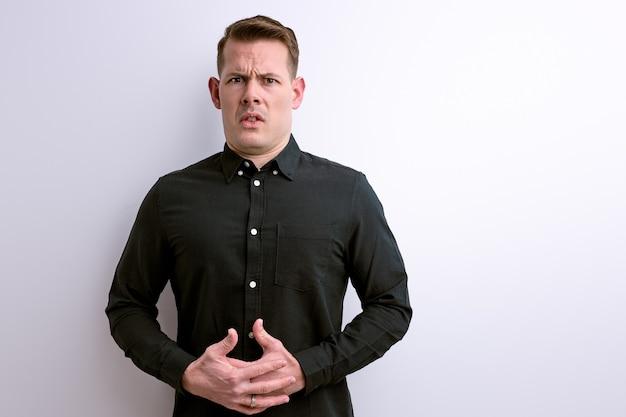 Man lijdt aan buikpijn op wit wordt geïsoleerd