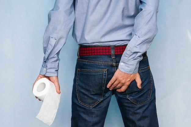 Man lijdt aan diarree houdt wc-papierrol in toilet vast. aan de andere kant houdt de man de kont vast.