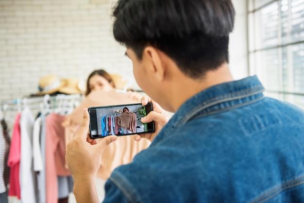 Man live videostreaming door smartphone om kleding te verkopen door modeblogger