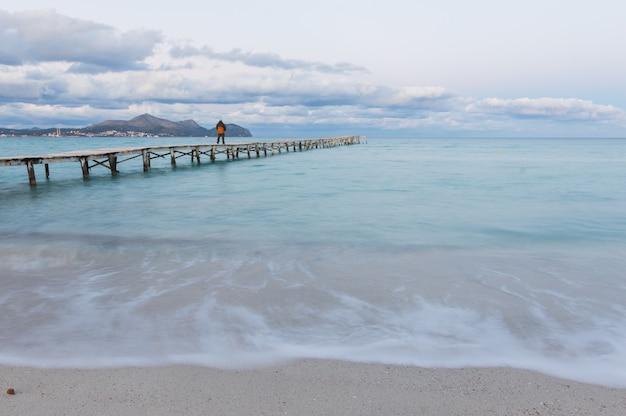 Man loopt langs een houten pier en geniet van het uitzicht op de oceaan