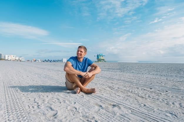 Man loopt langs het lege zandstrand van miami gelukkig knappe man toerist in vrijetijdskleding zittend op het zandstrand