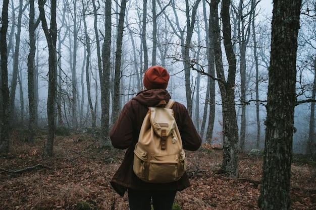 Man loopt op een donker pad door een spookachtig bos. hipster met een rugzak achter zijn rug gaat op reis
