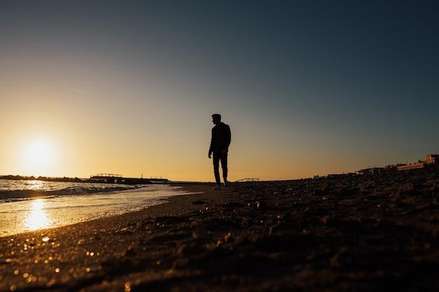 Man loopt op het strand naar een prachtige zonsondergang.