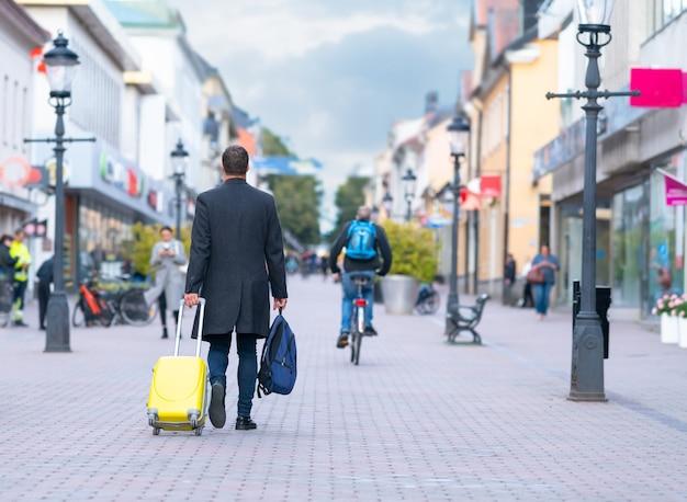 Man loopt weg met zijn koffer en bagage langs een voetpad in een stad tussen winkels en straatlantaarns