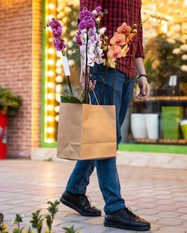 Man lopen met boodschappentas binnen nachtvlinder orchideeën phalaenopsis