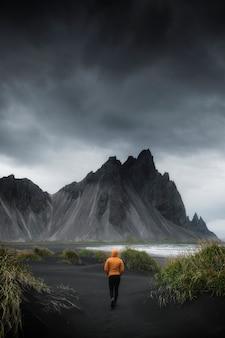 Man lopen op een zwart zandstrand, ijsland