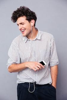 Man luisteren muziek in oortelefoons op smartphone