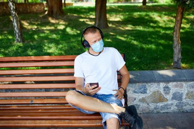 Man luisteren muziek met hoofdtelefoon, met behulp van smartphone dragen beschermend masker gezicht buiten in het park, levensstijl nieuw normaal, quarantaine, coronavirus