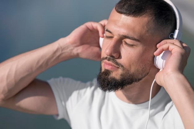 Man luisteren muziek met zijn ogen dicht