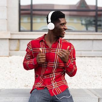 Man luisteren naar muziek en zitten