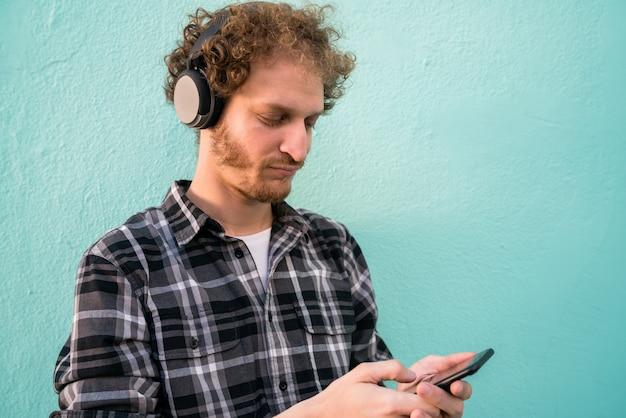 Man luisteren naar muziek met een koptelefoon en mobiele telefoon.
