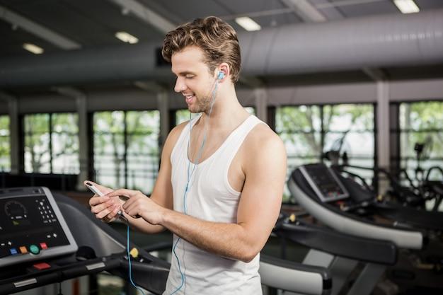 Man luisteren naar muziek op de loopband