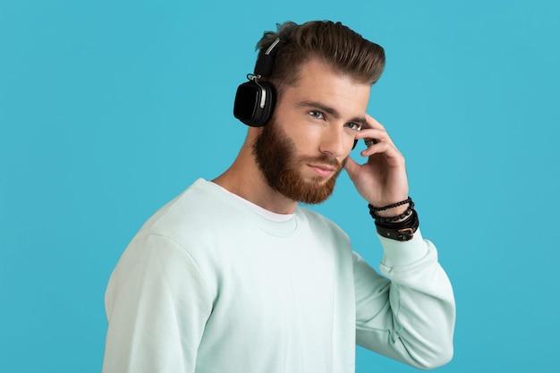 Man luisteren naar muziek op draadloze koptelefoon geïsoleerd op blauw