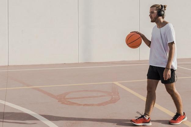 Man luisteren naar muziek op koptelefoon wandelen met basketbal in de rechtbank