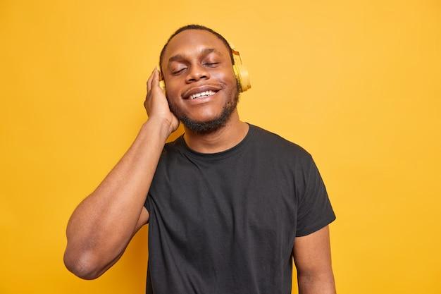 Man luistert graag naar favoriete muziek draagt draadloze koptelefoon op oren vangt elk stukje nummer gekleed in zwart t-shirt geïsoleerd op levendig geel