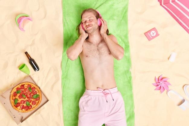Man luistert graag naar favoriete muziek via een koptelefoon terwijl hij op een groene handdoek ligt aan het zandstrand omringd door verschillende items heeft goede rust tijdens de zomervakantie