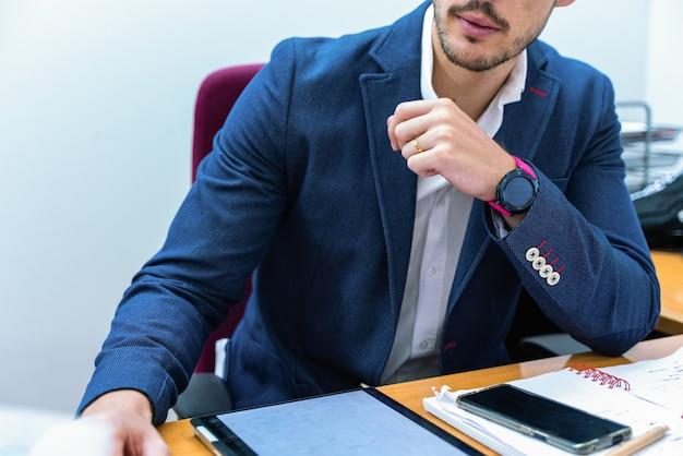 Man luistert naar zijn klanten op zijn kantoor terwijl hij over zaken praat
