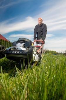 Man maaien, gras maaien op zijn enorme tuin, groen veld door de motortuinmaaier, tuinieren concept
