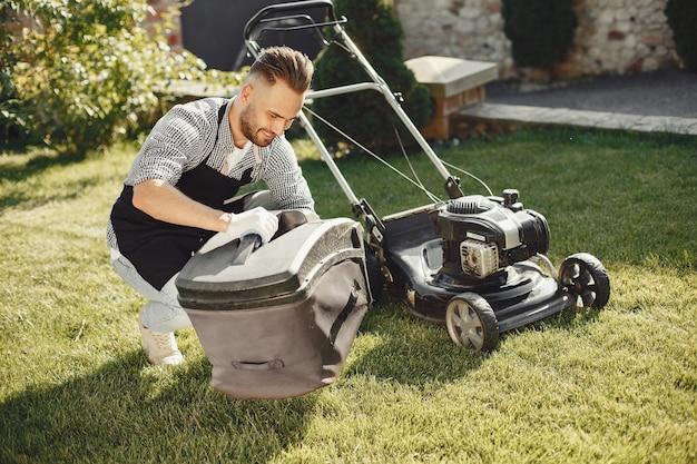 Man maaien gras met gazonverhuizer in de achtertuin. mannetje in een zwart schort. kerel repareert.