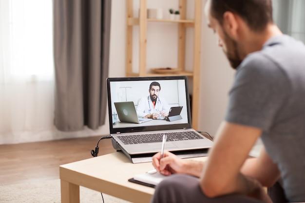 Man maakt aantekeningen op klembord in een videogesprek met zijn arts tijdens overleg in tijd van quarantaine.