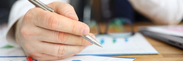 Man maakt bewerkingen leunend over financieel verslag