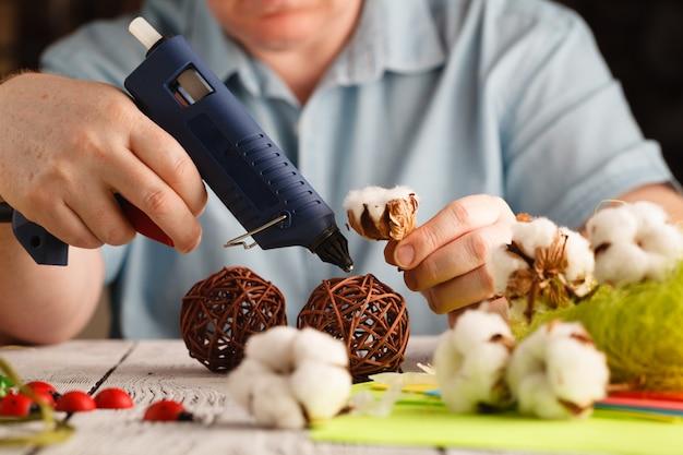 Man maakt bloemendecor met smeltlijmpistool