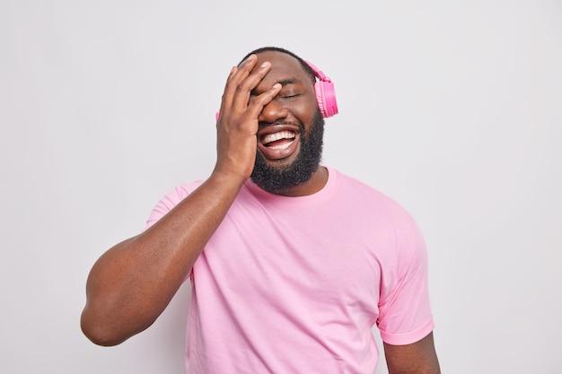 Man maakt gezicht palm lacht vrolijk luistert muziek via koptelefoon gekleed in casual t-shirt