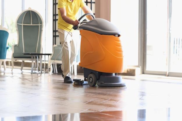 Man maakt hotellobby schoon met industriële stofzuiger