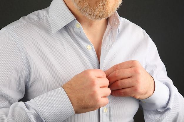 Man maakt knopen op zijn overhemd vast