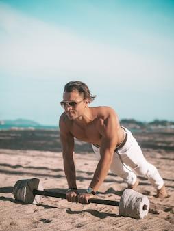 Man maakt push ups op het strand. spier mannelijk model