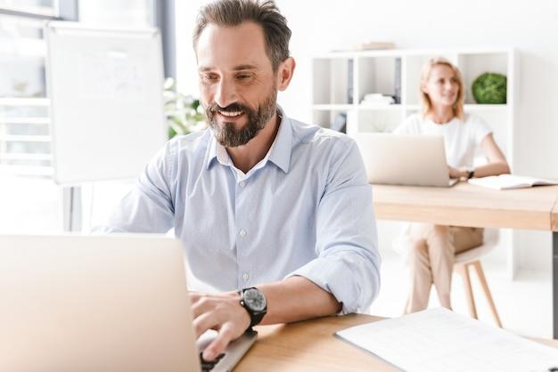 Man manager die op laptop werkt