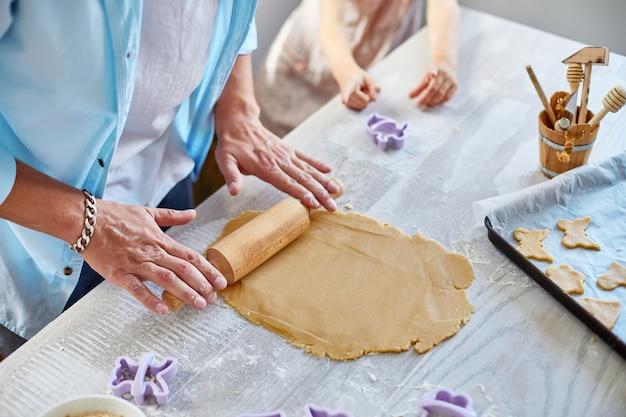 Man, mannetje rollen het deeg door rolspeld thuis in de keuken, voorbereiding voor koekjes, thuis koken.