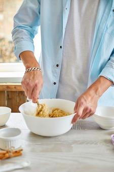 Man, mannetje vormen het deeg in kom a en thuis in de keuken kneden, koekjes voorbereiden, thuis koken.