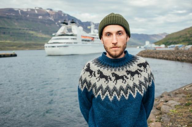 Man matroos in traditionele trui staan in de fjordhaven