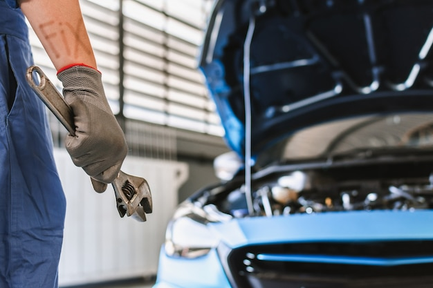 Man mechanic inspectie hold sleutel voor fix blauwe auto voor service onderhoudsverzekering