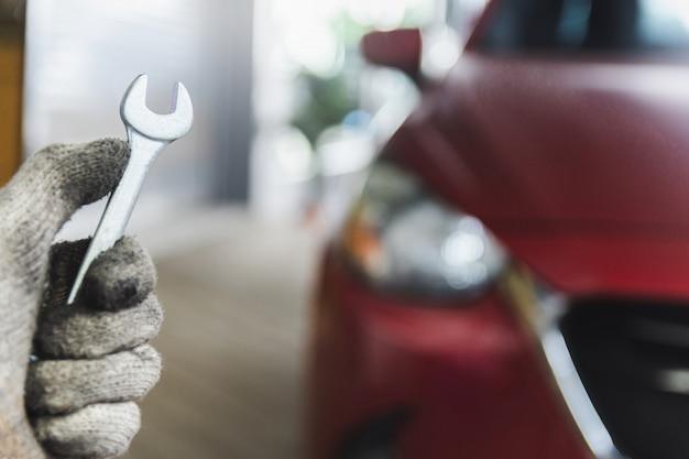 Man mechanische inspectie service onderhoud auto met moersleutel met zaklamp voor controle met klant vrouw hand wijzen controle motor in garage showroom dealer