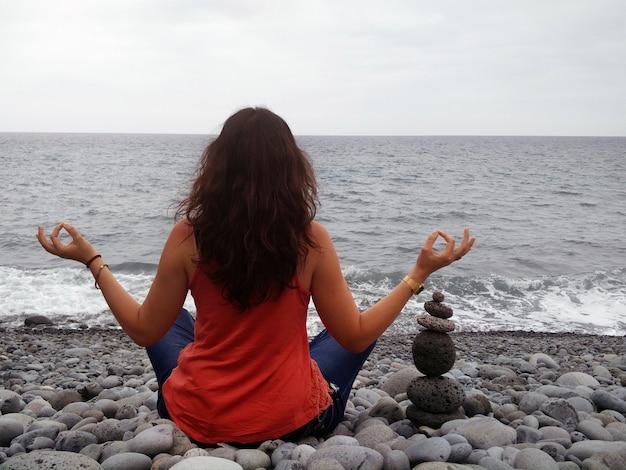 Man mediteert in kiezelstrand