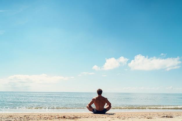 Man mediteert op het zandstrand uitzicht vanaf de achterkant