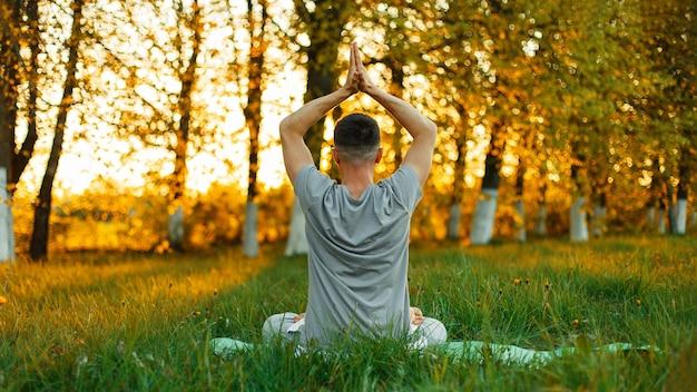 Man mediteren beoefenen van yoga in het park bij zonsondergang. gezonde levensstijl