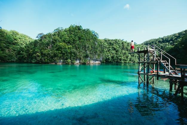 Man mediteren in de lagune in de ochtend, genietend van het uitzicht.