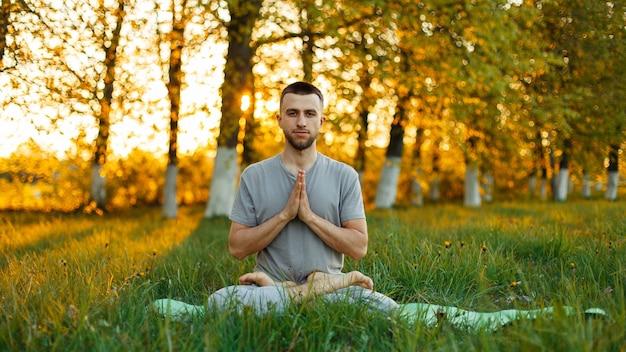 Man mediteren in een park bij zonsondergang. gezonde levensstijl