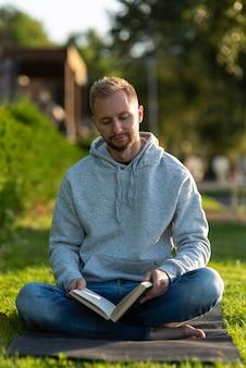 Man mediteren in het park tijdens het lezen